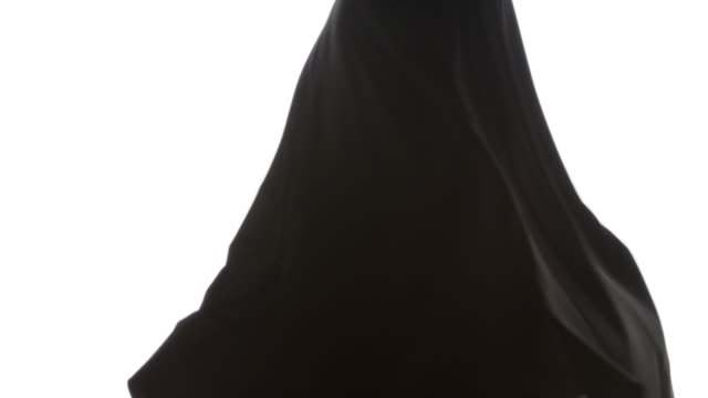 Hips and legs of black woman spinning in slow motion with long flowing dress