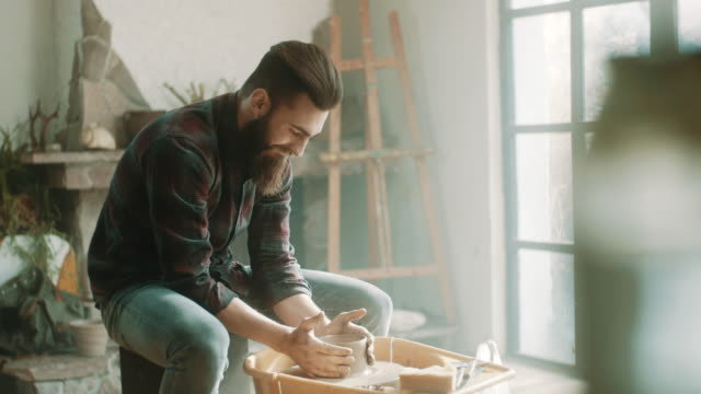 vídeos de stock e filmes b-roll de hipster artist using pottery wheel at atelier - escultor