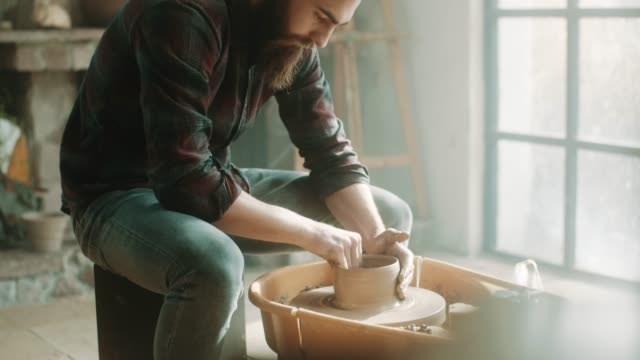 hipster artist using pottery wheel at atelier - potter stock videos and b-roll footage