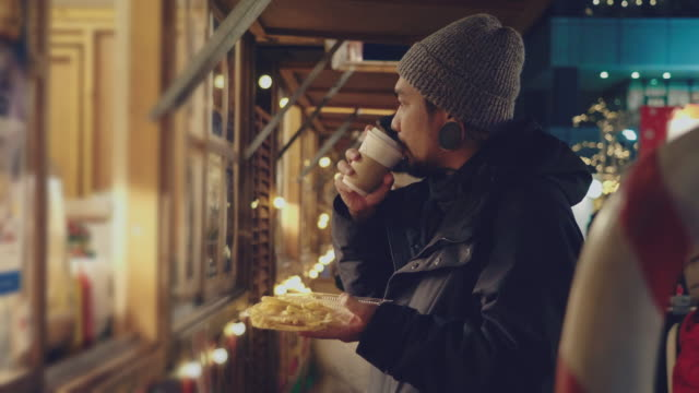 クリスマスマーケットファーストフードを買うヒップスターアジアマン - winter点の映像素材/bロール