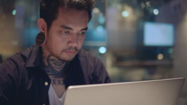 vidéos et rushes de hipster asiatique pigiste mâle utilisant son ordinateur portatif et travaillant au café - boucle d'oreille