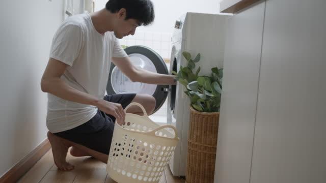 hipster asiatische mann wäschen zu hause - waschsalon stock-videos und b-roll-filmmaterial