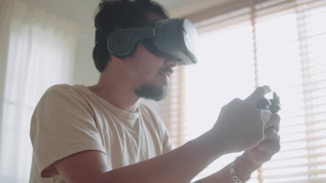 vídeos de stock, filmes e b-roll de hipster asiático vestindo vr e segurando joystick para jogar jogos no quarto em casa. - controle