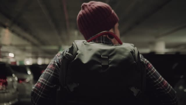 hipster backpacker walking in car park. - looking around stock videos and b-roll footage