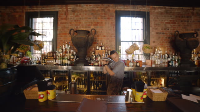 stockvideo's en b-roll-footage met hipster bartender shakes metal martini shaker - cocktail