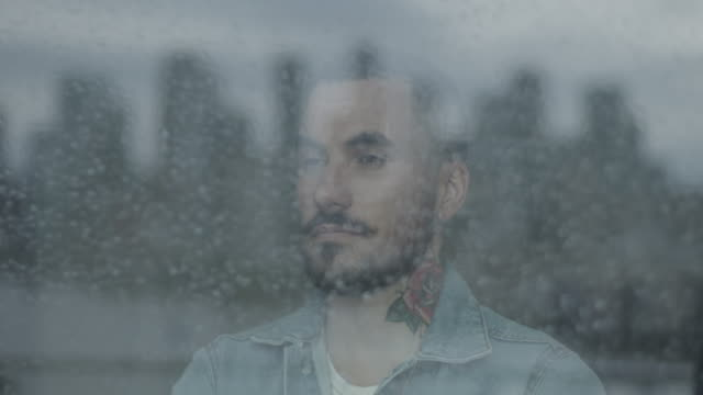 hipster bearded young adult male looking out of window on rainy day at view of city skyline - blick durchs fenster stock-videos und b-roll-filmmaterial