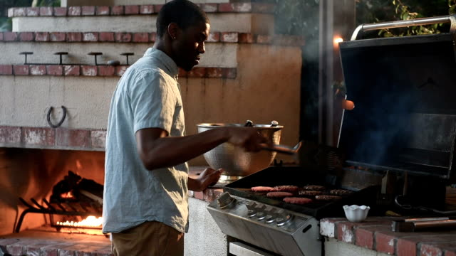 Hipster Black Male Grills at Backyard Summer BBQ