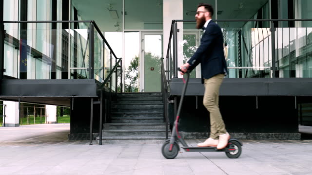 hipster businessman taking an electric scooter to work - scooter stock videos & royalty-free footage