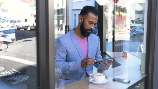 hipster businessman using technology in a coffee bar - color stock-videos und b-roll-filmmaterial