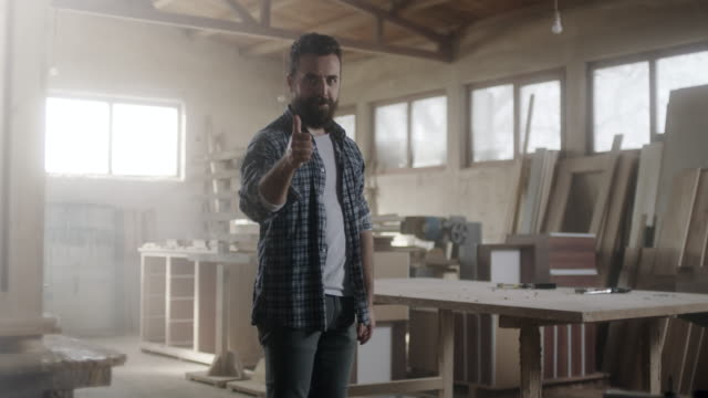 Hipster carpenter showing thumbs up at workshop