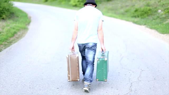 Slip a vita bassa portano la valigie lungo la strada