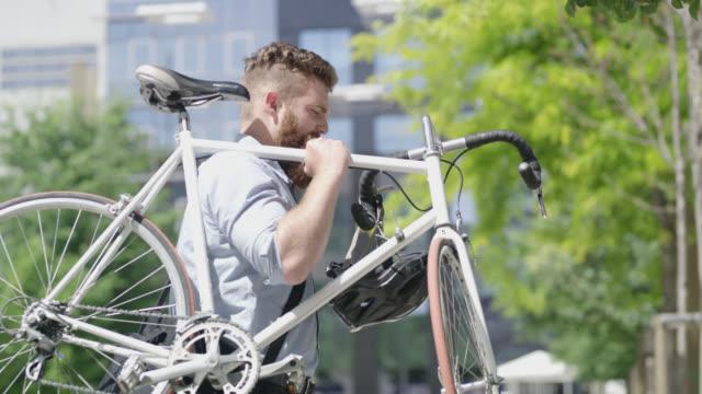 vídeos de stock, filmes e b-roll de hipster pan carregando sua bicicleta na cidade - carrying
