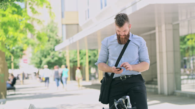 ds hipster checking his smart phone while riding his bicycle in the city - pedestrian zone stock videos & royalty-free footage