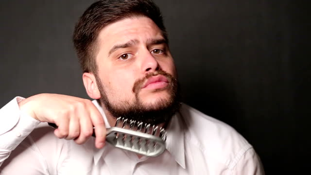 stockvideo's en b-roll-footage met hipster combing his beard - haarborstel