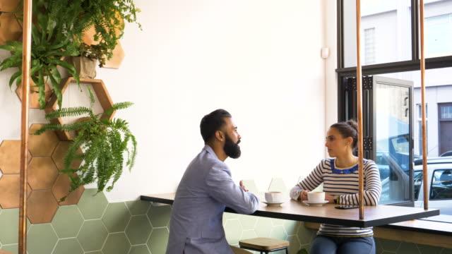 hipster couple sitting together in coffee bar - bar点の映像素材/bロール
