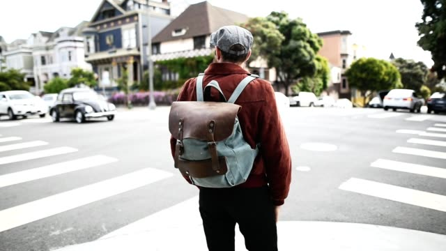 hipster crossing the street in san francisco - zaino da montagna video stock e b–roll