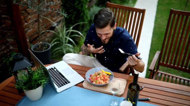 stockvideo's en b-roll-footage met hipster risotto buitenshuis eten tijdens het werken op de laptop - freelancer