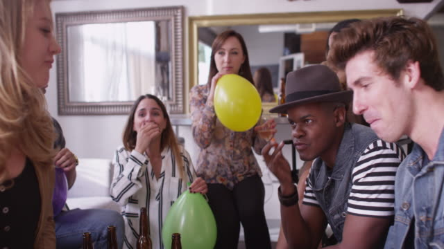 vídeos y material grabado en eventos de stock de hipster friends filling up helium balloons at party together and laughing - helio