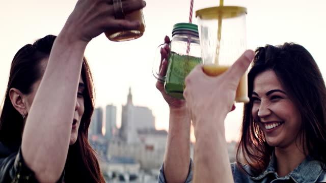 hipster-freunde treffen sich auf dem dach. trinken von sommergetränken - terrasse grundstück stock-videos und b-roll-filmmaterial