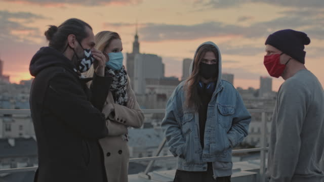 hipster friends meeting on a rooftop. social life during pandemic - safety stock videos & royalty-free footage