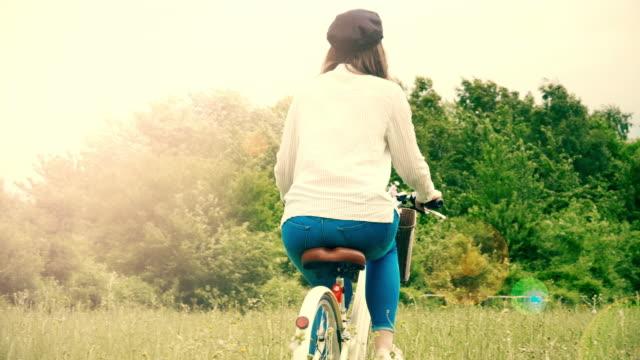 hipster mädchen fahrrad durch eine wiese. sicht nach hinten. - braunes haar stock-videos und b-roll-filmmaterial
