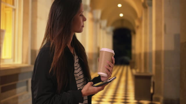 Hipster girl holding coffee while texting with cellphone in building hallway