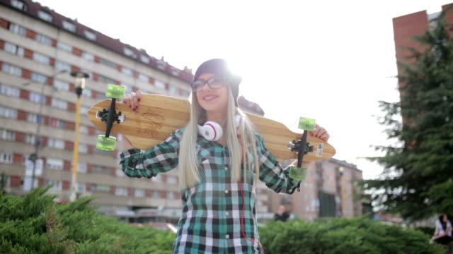 Hipster girl holding longboard