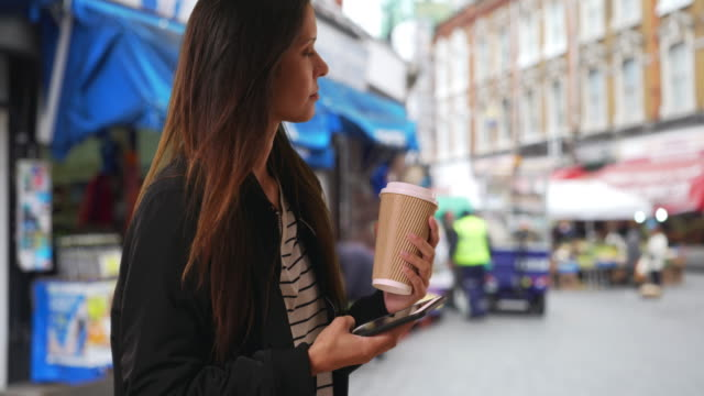 Hipster girl in bomber jacket texting with cell phone in London neighborhood