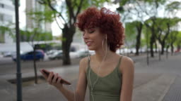 Hipster girl listening music and signing in the city