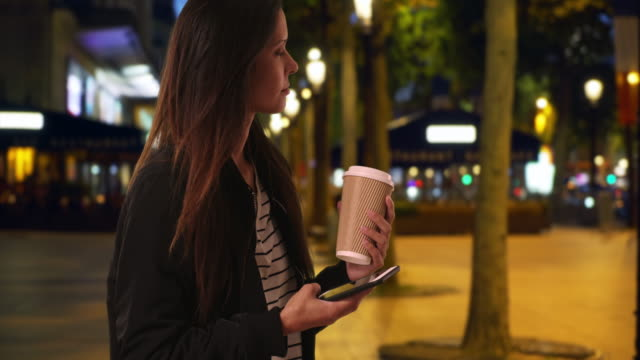 Hipster girl on the Champs-Elysees at night texting with cell phone