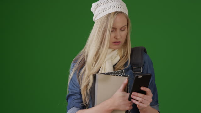 Hipster girl texting answers to social studies midterm on green screen