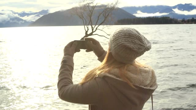 旅行の流行に敏感な女の子が携帯電話を用いた景観の写真を撮る - 冠雪点の映像素材/bロール