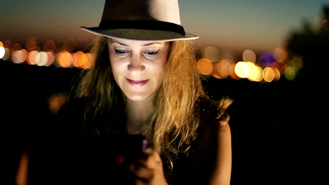 hipster girl using smart phone at night