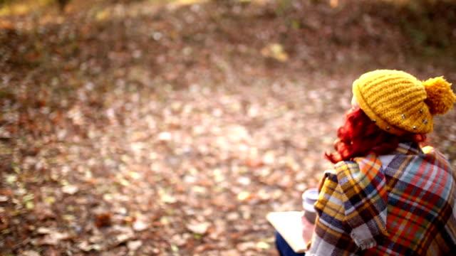 stockvideo's en b-roll-footage met hipster meisje met koffiekopje en boek, zittend op koffer - warme dranken