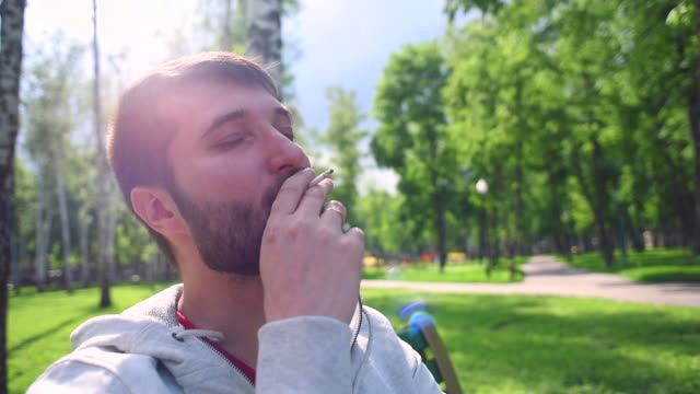 Hipster  guy smoking in the park