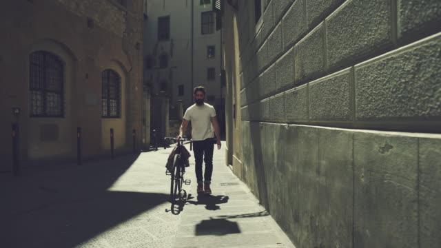 vídeos de stock e filmes b-roll de homem hipster com bicicleta em florença, itália - toscana