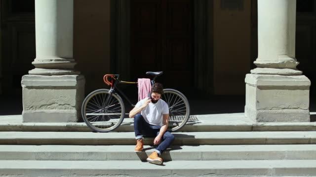 vidéos et rushes de hipster homme avec vélo à florence, italie - jeunes hommes