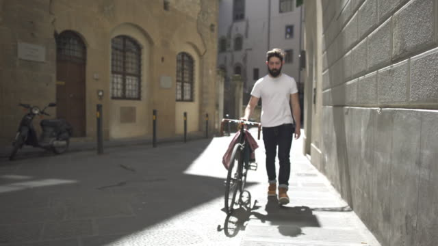 hipster guy with bicycle in florence, italy - one young man only stock videos & royalty-free footage