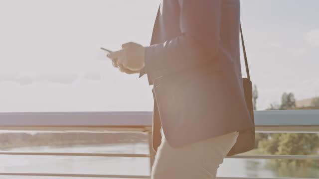 stockvideo's en b-roll-footage met slo mo hipster in een pak met behulp van zijn mobiele telefoon tijdens het lopen over de brug - mid volwassen mannen