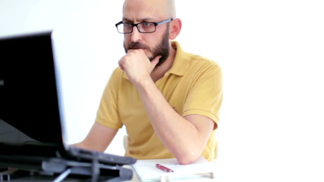 Hipster in yellow tshirt using laptop with positive expression