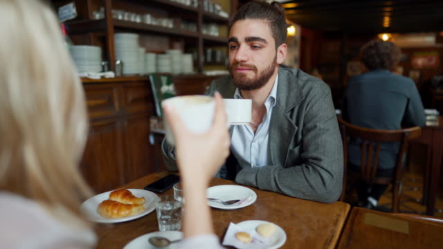 hipster latin couple sitting in cafe and talking over coffee and croissants - croissant stock videos & royalty-free footage