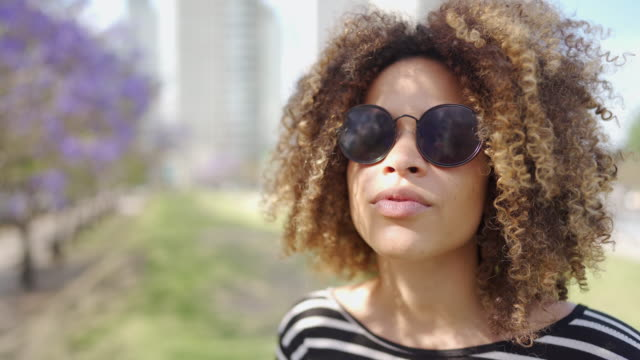 hipster latin woman with sunglasses standing in public park - big hair stock videos & royalty-free footage