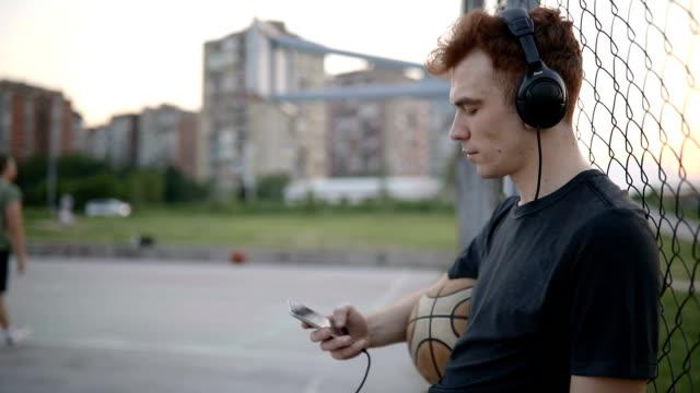 hipster lyssna på musik på en basket terräng - basketboll boll bildbanksvideor och videomaterial från bakom kulisserna