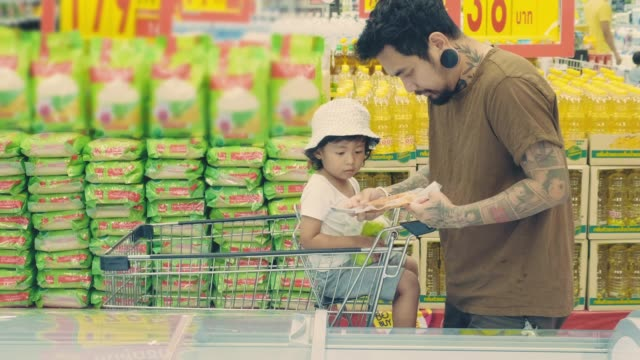 Hipster man and his son buying some frozen food at refrigerated section in local supermarket.