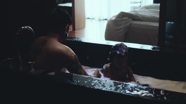 vídeos de stock e filmes b-roll de hipster man and little baby boy enjoying bath time in bathroom at home. - menino infancia pelado banheiro