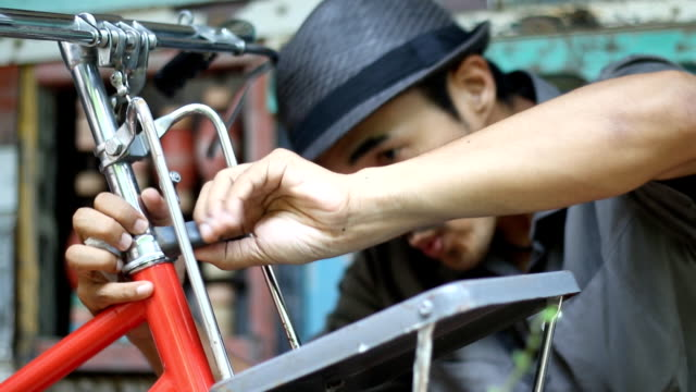 hipster man cleaning vintage bicycle