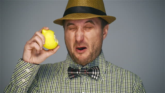 Hipster man eating ripe lemon