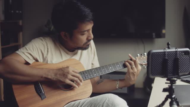 vídeos de stock, filmes e b-roll de hipster man dando aula de guitarra na internet com tutorial de vídeo em casa. - performance