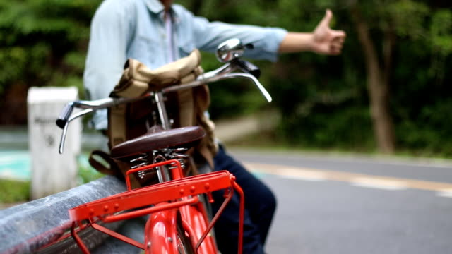 Hipster man hitch hiking along a countryside road after his vintage bicycle tire puncture