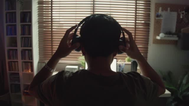 vidéos et rushes de homme hipster influenceur jouant le jeu vidéo pendant le vlog à la maison - casque